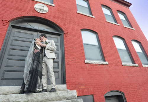 Bride and groom on steps of Old Labor Hall