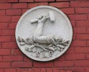 Granite plaque above the door of the Old Labor Hall showing the arm and hammer and the letters SLP