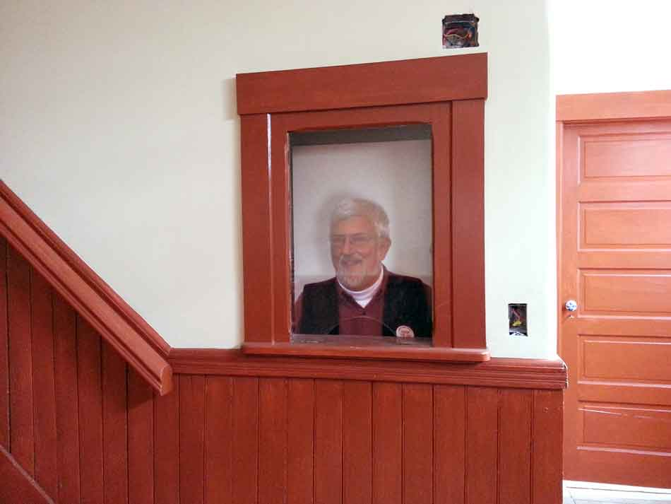 A picture of Chet Briggs in the historic ticket window newly reinstalled in the restored front entrance hallway