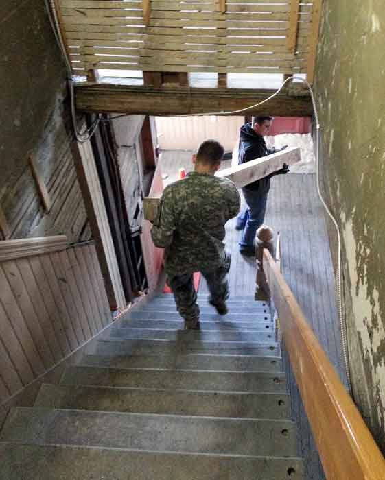Norwich cadets carrying beams downstairs