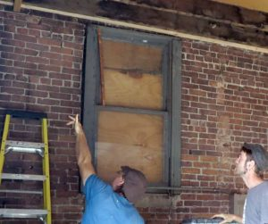 Carpenters looking a cracks in brickwork in the interior of the bakery