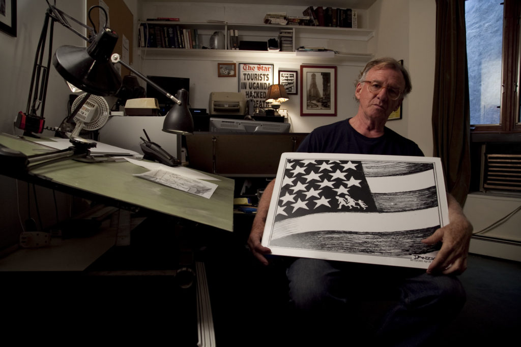Danziger in his studio with a US flag cartoon