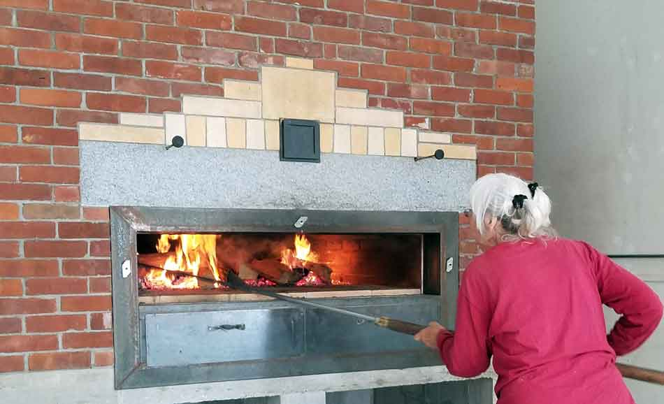 Carolyn Shapiro stoking the wood-fired oven in the Bakery