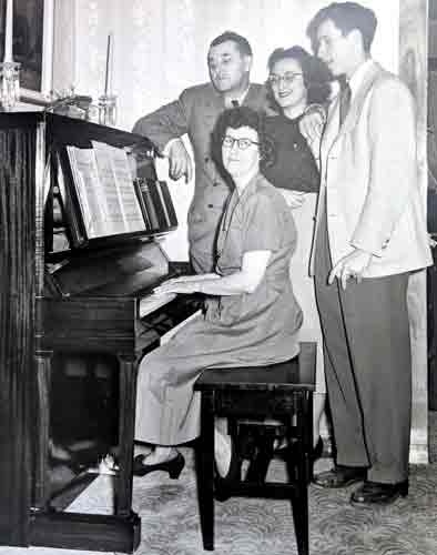 Corinne playing the piano for ,Deane,,Marian,and Tom Davis