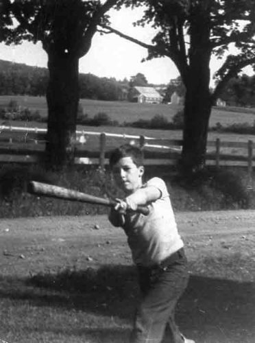 Tom as a young boy, swinging baseball bat